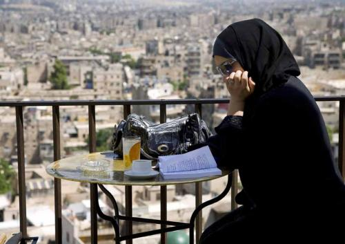 Young woman reading on a bar terrace. Aleppo, Syria (5/2009)